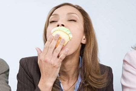 Woman binging on a cupcake.