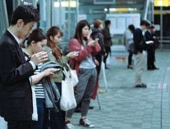 People standing around looking down at phones.